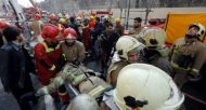Un pompier blessé évacué après l'effondrement d'un immeuble de 15 étages le 19 janvier 2017 à Téhéran  © AFP STR